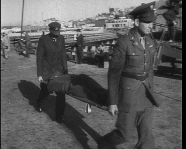 Stretcher carrying covered body of Bernard Paul Coy, who started the revolt of 1946.